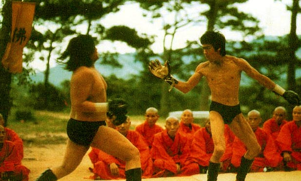 "Bruce waves ""Hi"" to Sammo Hung before hitting him with a spinning back kick"